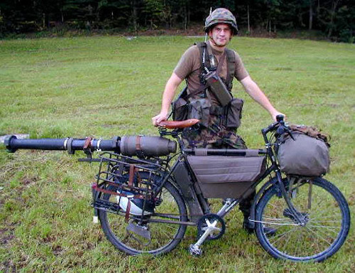 A Swiss soldier poses with his Modell-93 bicycle, circa 1999. In addition to a sprung leather saddle, it also carries a bazooka and a bicycle helmet.